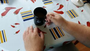 Man dricker kaffe vid köksbord.