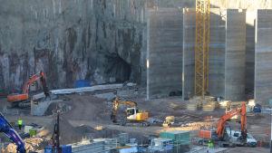 Grävskopor i arbete. I bakgrunden syns ingång till tunnel.