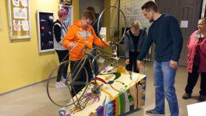 Sami Renberg, Pirjo Lehtinen och Petri Helmi spelar på cykelinstrumentet på utställningen på Vimma.