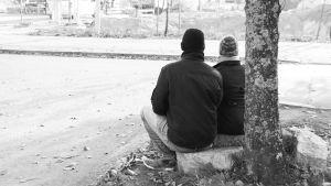 två personer sitter på gatstenar, svartvit bild