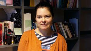 Pia Mikander framför en bokhylla.