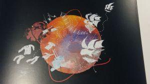 En bild på en bokpärnm med ett jordklott fåglar och tröjor som flyger. Kanske de symboliserar migration?