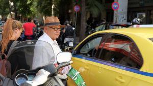 Äldre man säljer lotter på gatan i Aten.