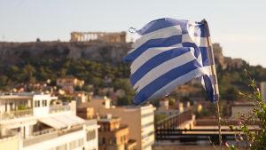 En trasig grekisk flagga med Akropolis i bakgrunden.