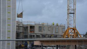En lyftkran lyfter byggmaterial på plats på bostäderna på Fabriksudden i Hangö.