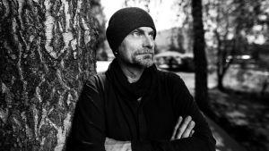 Jarmo Lampela poseeraa puuhun nojaten, katseen suunta kamerasta oikeaan viistoon.