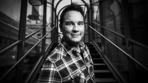 Mies, Matti Kajander poseeraa ja hymyilee kameralle rappukäytävässä.