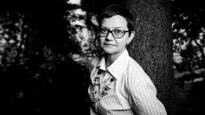 Nainen, Anna-Maija Halonen nojaa puuhun ja katsoo kameraan.