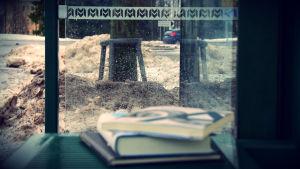 Böcker på busshållplats och slaskigt väder.