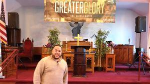 Pastor Pablo Pizarro står framför altaret i sin kyrka i Newark i USA.