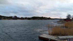 solen tittar fram över öar i skärgården, men det är mörka moln och stormigt väder i november.