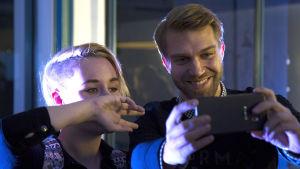 Jarkko Niemi poseeraa fanin kanssa kännykkäkameralle Syke-fanitilaisuudessa.