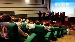 Ylen auditoriossa istuu Syke-sarjan faneja, lavalla seisovat sarjan näyttelijät.