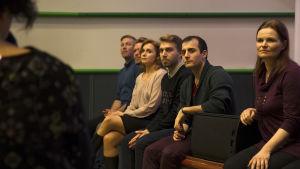 Syke-sarjan näyttelijät istuvat ja kuuntelevat.