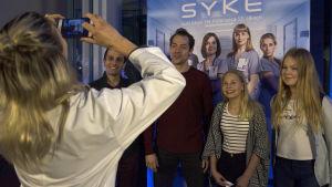 Syke-sarjan näyttelijät poseeravat kännykkäkameralle faniensa kanssa.