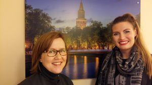 Sari Ruusumo och Lotta Bäck från Visit Turku framför en plansch över Åbo Domkyrka och Biblioteksbron.
