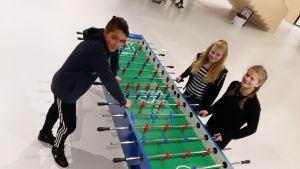 Tommy Weckström Pernilla Tackman och Ellen Sillman står vid ett av spelborden i skolcentret Nickby hjärta i Sibbo