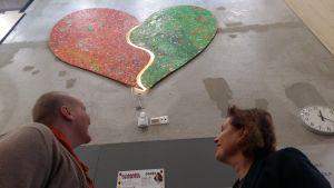 Rektorerna i Nickby hjärta ser upp mot skolans symbol, ett hjärta, på skolväggen.