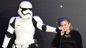 Carrie Fisher håller en Starwars-krigare, även kallad Stormtrooper, i handen och trycker den mot sin kind i december 2015.