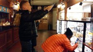 Bloggarna Otto Lilja och Yuki Ng fotograferar bakverk i saluhallen i Åbo.