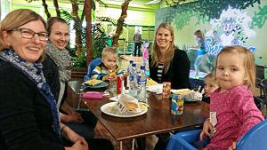Mormor, barn och barnbarn tar en välbehövlig paus i inomhuslekparken.