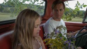 Far och dotter sitter i en bil med en bukett blommor mellan sig.