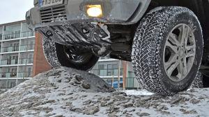 Närbild på terrängbil där däcken är uppkörda på en snöhög.