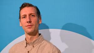 Pekka Strang poserar framför en blå bakgrund, tittar in i kameran.