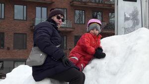 Irene Oskarsson med barnbarnet Hugo i en snödriva i Stockholm.