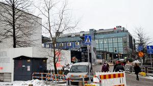 Glaspalatsets pilträd omgett med byggställningar, med Narinken och Kampens köpcentrum i bakgrunden.
