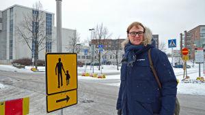 Nikas Aalto-Setälä poserar framför en gul skylt som dirigerar om forgängartrafiken.