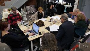 Ihmiset istuvat pöydän ympärillä, pöydällä papereita ja kannettavia tietokoneita.