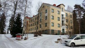 Gammalt gult höghus i sten i byn Aijala i Kisko.