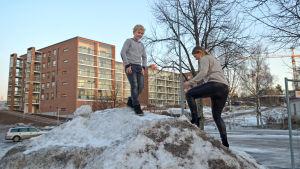 Oliver Piha står på en snöhög medan mamma Tanja Piha klättrar uppför den.