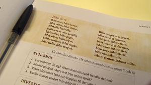 Foto på en lärobok i latin, med en penna.