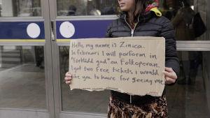 Zinica håller en skylt utanför tunnelbanestationen, där det står att hon ger bort 2 gratisbiljetter till Folkoperan.