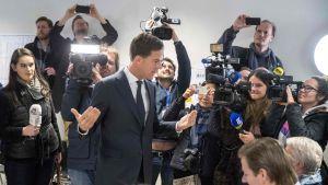 Mark Rutte omgiven av journalister på valdagen.