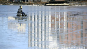 En pilkare sitter på den blanka isen i dagsljus utanför academill och silorna. Man ser reflektionen av silorna i isen.