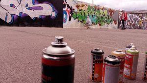 Sprayburkar som en graffitiartist använder på en vägg vid ett bygge.