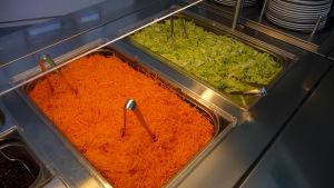 Rivna morötter och isbergssallat i serveringslådor.
