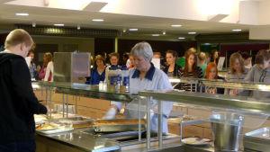 Elever köar för att ta mat ur serveringskärlen.