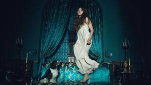 Jenna Coleman on kuningatar Viktoria ja hyppii sohvalla ja koira katsoo vieressä.