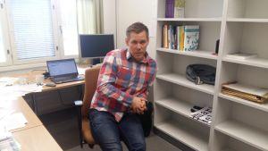 Forskningschef Lauri Rapeli sitter vid sitt arbetsbord på Åbo akademi.