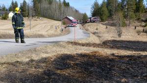 brandman står på pohjakkavägen och ser på bränd åker, i bakgrunden räddningsfordon
