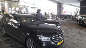 En taxichaufför med ryggen mot kameran, utanför sin taxibil som saknar logga.