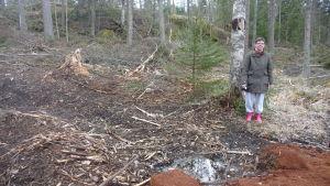 Tanja Westerholm står i en skog i Kristinestad som efter avverkning ser ut som ett bombnedslag enligt henne.