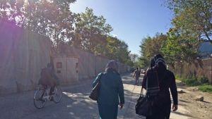 Två kvinnor och en cyklist på en sandväg i Kabul invid en hög mur.