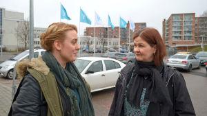 My Ström och Mette Strauss på parkeringsplats, med Yle-flaggor i bakgrunden.