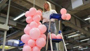 Minna Palmqvist står på en stege och hänger upp rosa ballonger i en kedja som hänger från taket i Wee-Gee-huset
