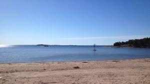 Sandstrand i Hangö med blått vatten och blå himmel. Stranden heter Plagen.